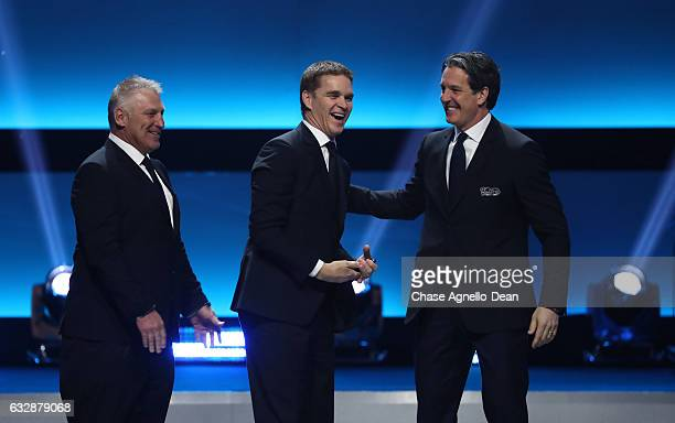 Former NHL players Brendan Shanahan far right and Luc Robitaille shake hands onstage as Brett Hull looks on during the NHL 100 presented by GEICO...