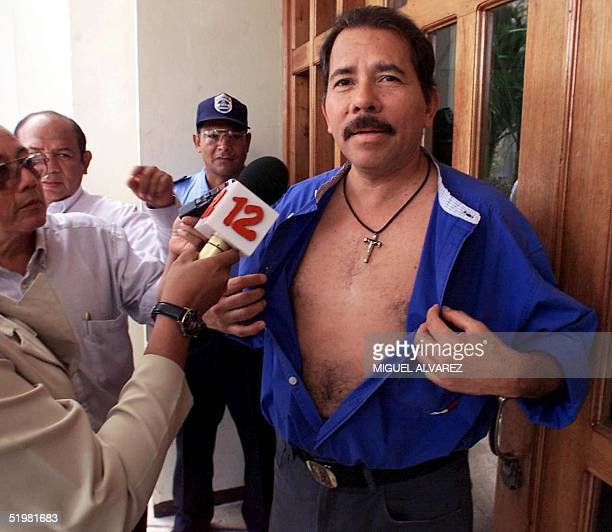 Former Nicaraguan President and current presidential candidate Daniel Ortega with the Sandinista Front of National Liberation opens his shirt to show...