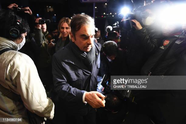 TOPSHOT Former Nissan Chairman Carlos Ghosn and his wife Carole are surrounded by members of the press as they arrive at their residence in Tokyo on...
