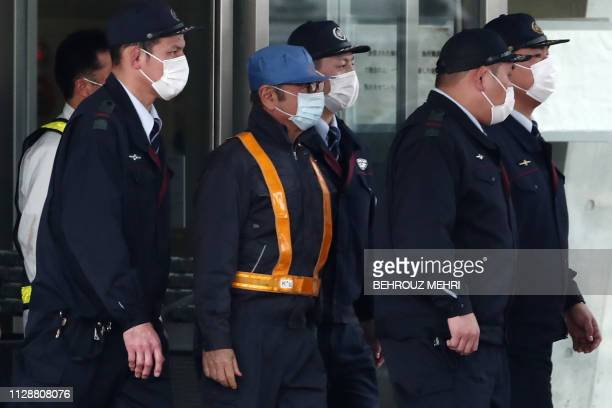 TOPSHOT Former Nissan chairman Carlos Ghosn is escorted as he walks out of the Tokyo Detention House following his release on bail in Tokyo on March...