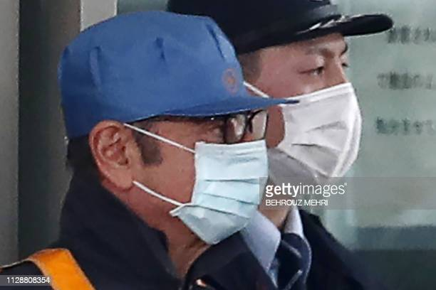 Former Nissan chairman Carlos Ghosn is escorted as he walks out of the Tokyo Detention House following his release on bail in Tokyo on March 6 2019...