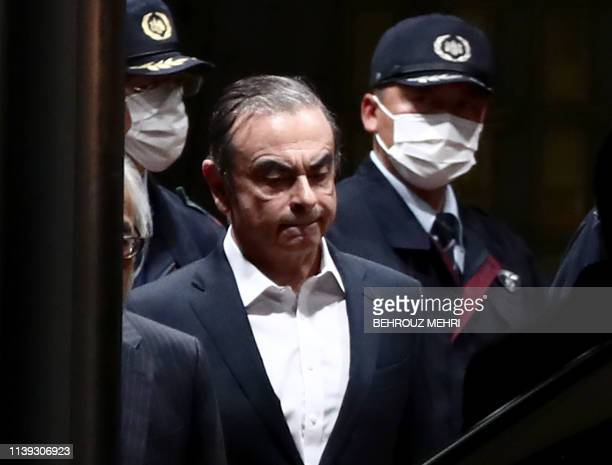 TOPSHOT Former Nissan chairman Carlos Ghosn is escorted as he walks out of the Tokyo Detention House following his release on bail in Tokyo on April...