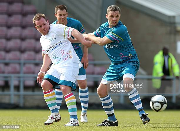 Former Northampton Saints player Paul Diggin plays the ball under pressure from Former Northampton Town FC player Ray Warburton during the Leon...