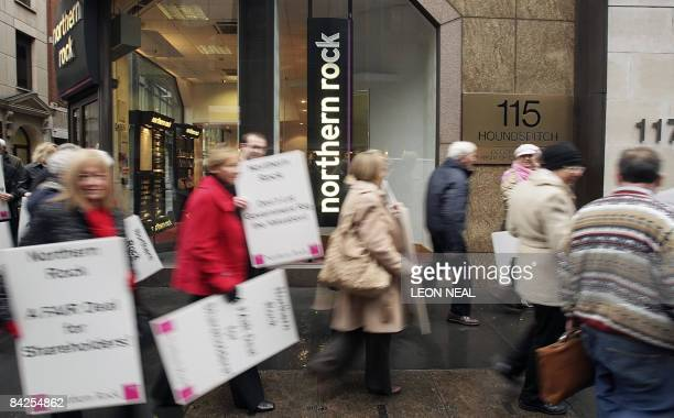 Former Northern Rock shareholders and their representatives protest outside a branch of the bank on Houndsditch in London on January 12 2009 They...