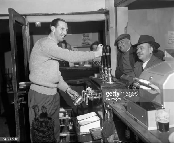 Former Notts County and England centre forward Tommy Lawton pulling pints behind the bar at the Magna Carta Inn at Lowdham Nottinghamshire where he...