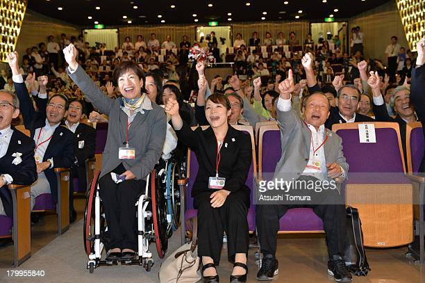 Former Olympic athletes Hiromi Miyake and Yoshiyuki Miyake cheer in support of Tokyo's bid for the 2020 Summer Olympic Games with the other audience...
