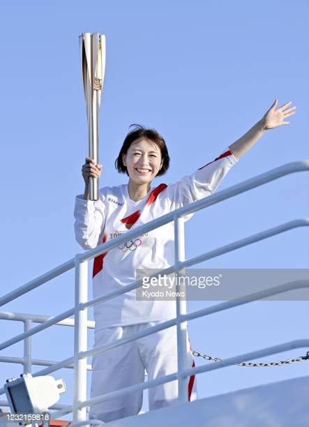 Former Olympic badminton player Kumiko Ogura waves from a ferryboat off Toba in Mie Prefecture, central Japan, on April 7 while carrying the Olympic...