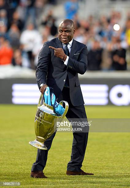 Former Olympique de Marseille player Basile Boli gestures on the field before the start of the French L1 football match Olympique de Marseille versus...