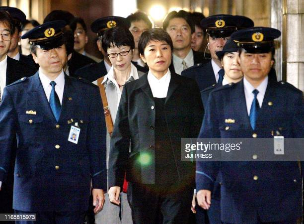 Former opposition lawmaker Kiyomi Tsujimoto surrounded by Diet guards enters the Diet building to testify at the Lower House's budget committee...
