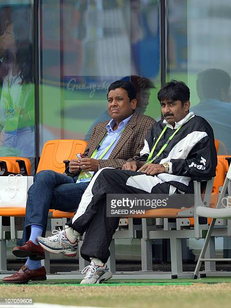 Former Pakistan cricket team captain Javed Miandad watches the cricket quarterfinal match between Pakistan and China with an unidentified official at...