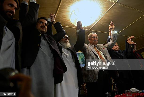 Former Pakistani nuclear scientist and chairman of TehreekeTahafuz Pakistan party Abdul Qadeer Khan raises his hands with Syed Munawar Hassan...