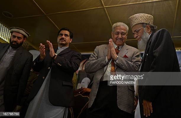 Former Pakistani nuclear scientist and chairman of TehreekeTahafuz Pakistan party Abdul Qadeer Khan claps as Syed Munawar Hassan President of...