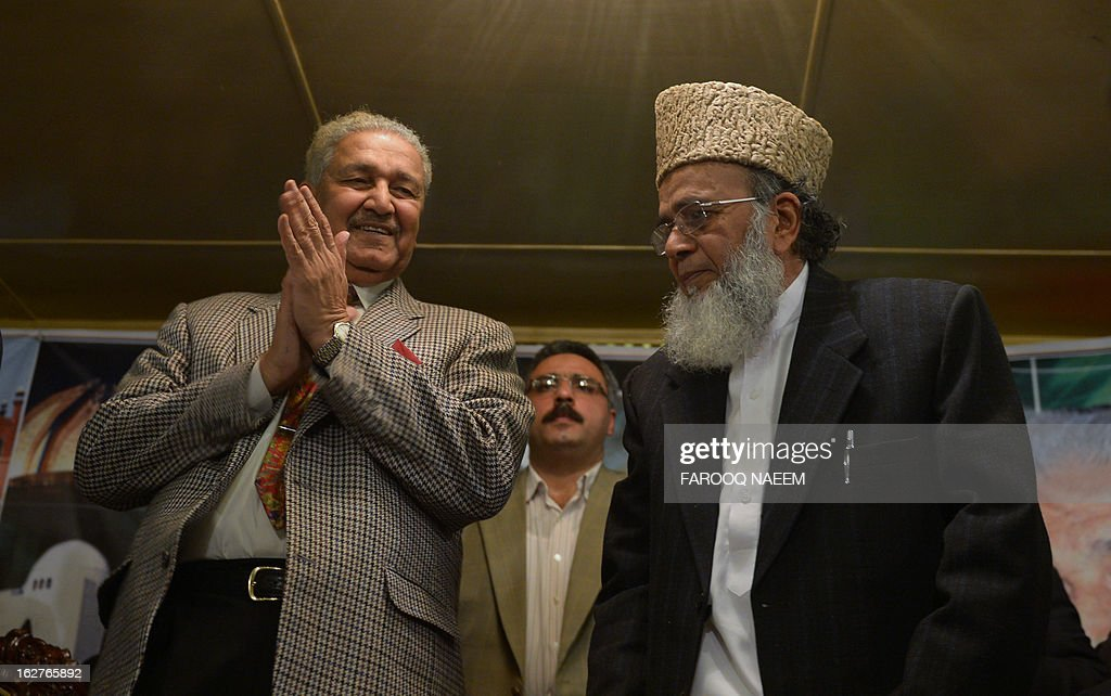 Former Pakistani nuclear scientist and chairman of Tehreek-e-Tahafuz Pakistan party, Abdul Qadeer Khan (L), claps as Syed Munawar Hassan (R) President of Jamaat-e-Islami party stands to give a speech during a public meeting in Islamabad on February 26, 2013. Khan has registered a new political party last year to contest for the first time general elections expected next year, officials said. AFP PHOTO/Farooq NAEEM