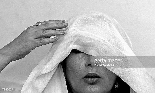 Former Pakistani premier Benazir Bhutto adjusts her head scarf during a press conference at her house in Karachi on October 21, 2007 in Karachi,...