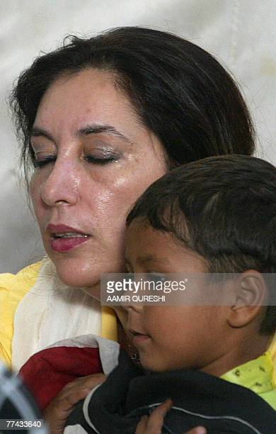 Former Pakistani premier Benazir Bhutto comforts a child who lost his father in a suicide attack during a praying at her house in Karachi 21 October...