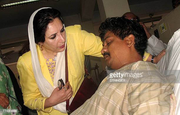 Former Pakistani premier Benazir Bhutto comforts an injured man in Karachi 21 October 2007 during a visit to Jinnah hospital to offer support to some...