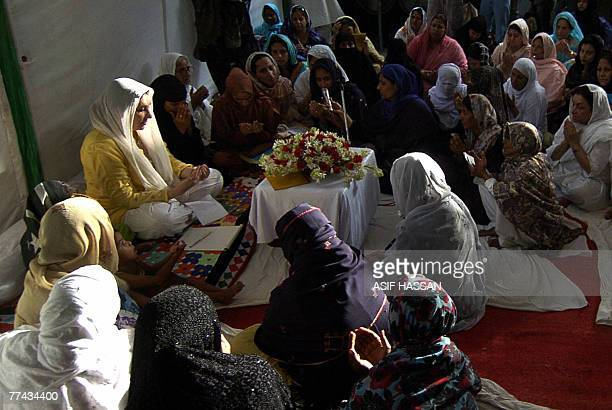 Former Pakistani premier Benazir Bhutto prays with relatives of those killed in a suicide attack during her homecoming procession in Karachi 21...