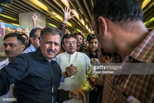Former Pakistani president Pervez Musharraf is greeted by supporters as he is ushered through by security after landing on Pakistani soil at Jinnah...
