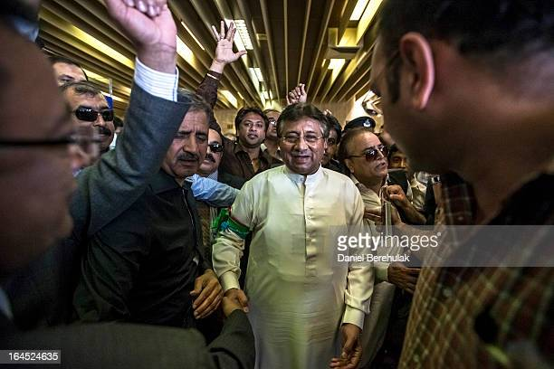 Former Pakistani president Pervez Musharraf is greeted by supporters after landing on Pakistani soil at Jinnah International airport on March 24,...