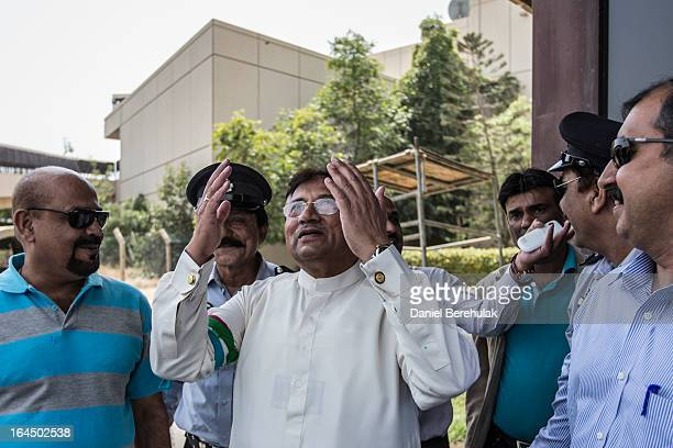 Former Pakistani president, Pervez Musharraf raises his hand in prayer as he looks to the sky after landing on Pakistani soil, at Jinnah...