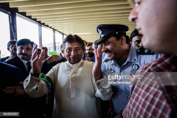 Former Pakistani president, Pervez Musharraf raises his hands in thanks as he is greeted by supporters and ushered through by security after landing...