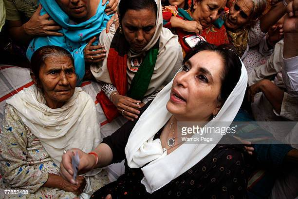 Former Pakistani Prime Minister and head of Pakistan People's Party Benazir Bhutto talks with the family of PPP supporter Zaheer Abbas who was killed...