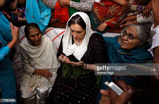 Former Pakistani Prime Minister and head of Pakistan People's Party Benazir Bhutto prays with the family of PPP supporter Zaheer Abbas who was killed...