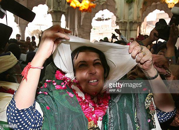 Former Pakistani prime minister Benazir Bhutto adjusts her scarf as she arrives at a shrine of Islamic saint Syed Ali bin Osman AlHajvery popularly...