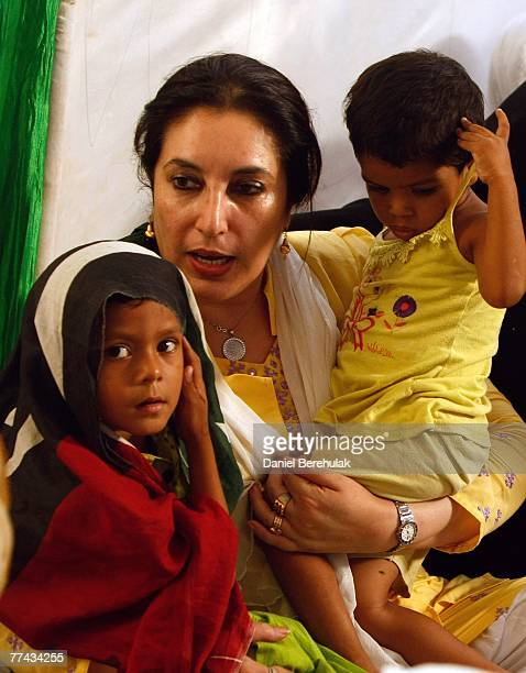 Former Pakistani prime minister Benazir Bhutto comforts children who lost their father in the suicide attack aimed at her three days ago during a...
