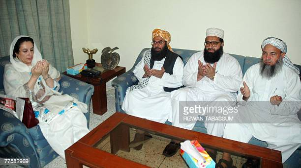 Former Pakistani prime minister Benazir Bhutto prays with Jamiat UlemaeIslam leaders at her residence in Karachi 23 October 2007 for those killed in...