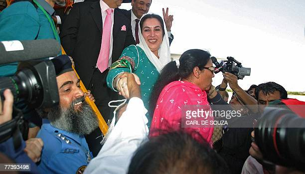Former Pakistani Prime Minister Benazir Bhutto shakes hands with supporters as she lands at Karachi international airport after leaving Dubai 18...