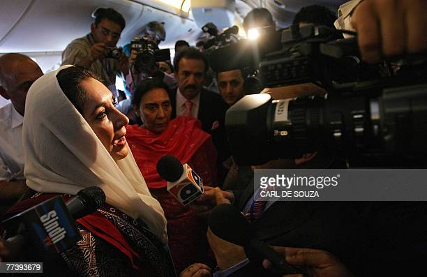Former Pakistani Prime Minister Benazir Bhutto talks to journalists during her flight to Karachi international airport after leaving Dubai 18 October...