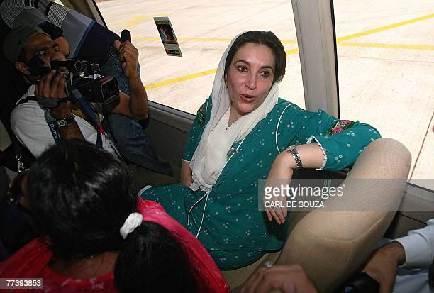 Former Pakistani Prime Minister Benazir Bhutto talks to journalists onboard her private minibus after landing at Karachi international airport after...