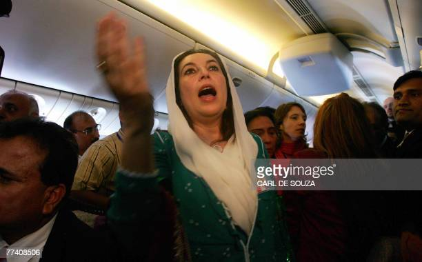 Former Pakistani Prime Minister Benazir Bhutto talks to journalists onboard a flight to Karachi international airport after leaving Dubai 18 October...