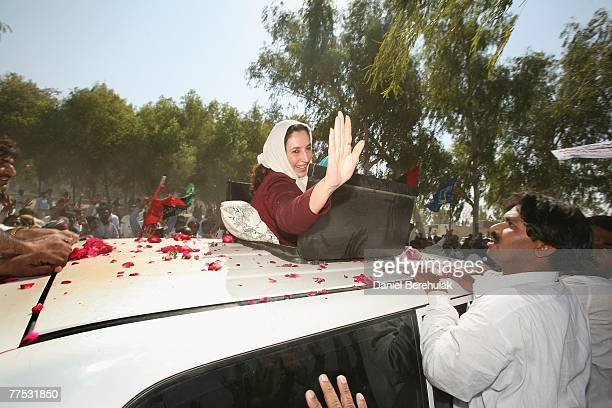 Former Pakistani Prime Minister Benazir Bhutto waves to supporters after visiting the Bhutto family mausoleum on October 27, 2007 near Larkana,...