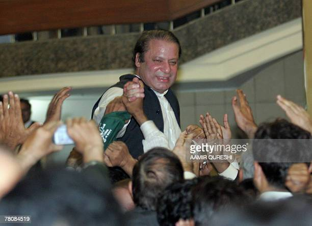 Former Pakistani prime minister Nawaz Sharif reaches out to his supporters outside the Allama Iqbal International airport in Lahore 25 November 2007...