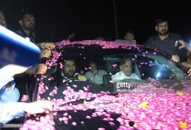 Former Pakistani Prime Minister Nawaz Sharif sits in a vehicle alongside his younger brother Shahbaz Sharif following his release from Adiala prison...
