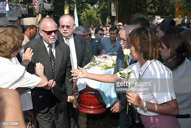 Former Paraguayan President Raul Cubas receives condolences as he arrives at the cemetery carrying the coffin of his daughter Cecilia Cubas in...
