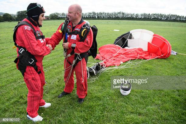 Former paratrooper Ted Pieri shakes hands with Cpl Tom Blakey after completing a tandem skydive at the Old Sarum airfield on August 10, 2017 in...