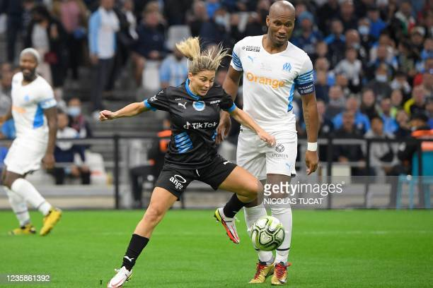 Former Paris Saint-Germain's French defender Laure Boulleau fights for the ball with former Ivorian football player Didier Drogba during the charity...
