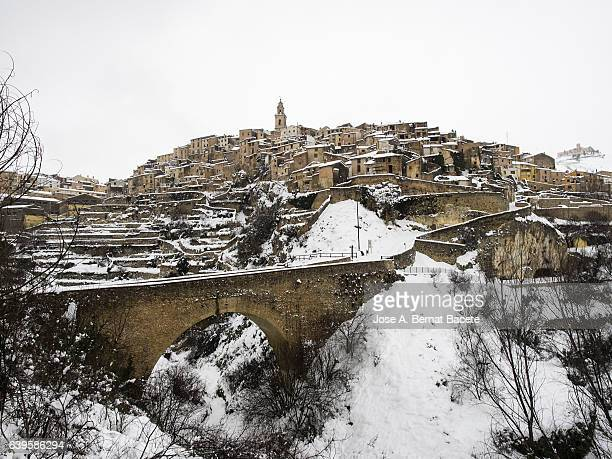 Former people of medieval construction snowed in winter, placed on a hill with a bridge of access