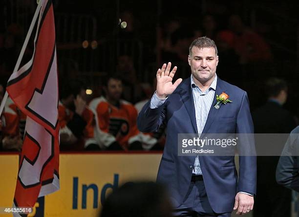 Former Philadelphia Flyer Eric Lindros acknowledges the crowd while walking onto the ice during the Eric Desjardins Flyer Hall Of Fame induction...