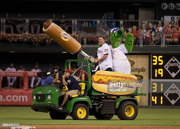 Former Philadelphia Phillies player Jim Thome shoots hot dogs with the Phillie Phanatic at the end of the fifth inning against the Colorado Rockies...