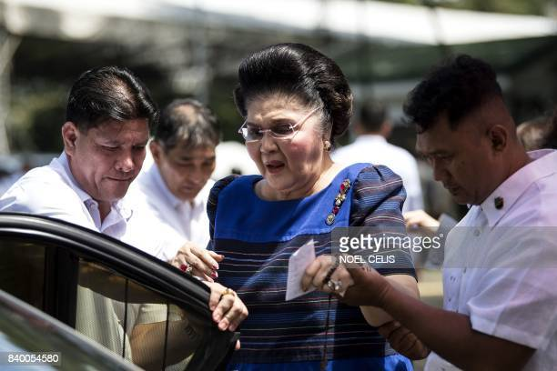 Former Philippine first lady and now congresswoman Imelda Marcos is assisted to her car after visiting the tomb of former Philippine president and...