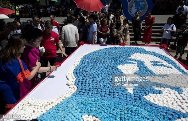Former Philippine first lady Imelda Marcos and her daughter Imee look at an image of the late dictator Ferdinand Marcos made out of cupcakes during...