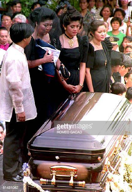 Former Philippine first lady Imelda Marcos holds the Philippine flag as she stands before the bronze coffin bearing the remains of her husband,...
