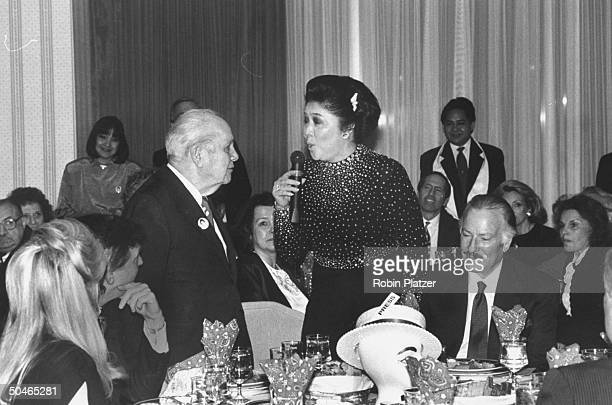 Former Philippine First Lady Imelda Marcos singing Happy Birthday to 80yearold columnist Joey Adams at his party part obsc are Donald Trump and Marla...