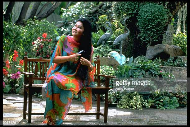 Former Philippine First Lady/congresswoman Imelda Marcos brushing hair while sitting on bench in garden prob. At home.