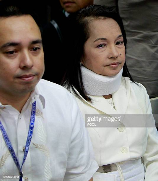 Former Philippine President and now Congresswoman Gloria Macapagal Arroyo sits with her son and Congressman Diosdado Dato Arroyo as she waits at the...