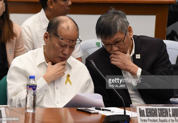 Former Philippine President Benigno Aquino reads a document next to former executive secretary Paquito Ochoa during the continuing hearing on the...
